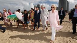 Pangeran Charles bersama istrinya, Duchess of Cornwall Camilla berjalan di atas pasir pantai saat mengunjungi Broadbeach di Gold Coast, Australia, Kamis (5/4). Istri Pangeran Charles itu terlihat berjalan tanpa alas kaki. (AFP PHOTO/POOL/Mark Metcalfe)