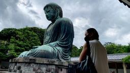 Seorang perempuan bermasker mengunjungi The Great Buddha atau yang biasa disebut Kamakura Daibutsu di kuil Kotoku-in di Kamakura, Prefektur Kanagawa, Jepang, Sabtu (20/6/2020). Patung Buddha dari perunggu yang menjulang dengan tinggi 13,35 meter ini didirikan tahun 1252. (Behrouz MEHRI/AFP)