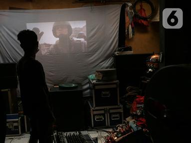 Adul (29) mengecek video di sebuah layar di gudang rumahnya di Jakarta, Rabu (28/4/2021). Sebelum masa pandemi, industri layar tancap memang perlahan mulai redup. (Liputan6.com/Johan Tallo)