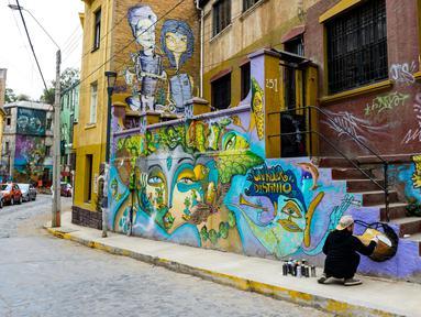 Seniman Sammy Espinosa menyelesaikan mural jalanan di Valparaiso, Chile, 9 April 2019. Valparaiso menjadi galeri seni terbuka raksasa. (Martin BERNETTI/AFP)