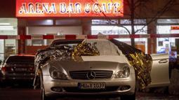 Sebuah mobil yang rusak terparkir di tempat penembakan di depan sebuah bar di Hanau, Jerman, Kamis, (20/2/2020). Polisi di Jerman menangkap satu orang terkait penembakan massal di dua bar hookah di Hanau, Rabu malam.  (AP Photo/Michael Probst)
