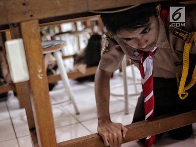 Sejumlah siswa berlindung di bawah meja saat simulasi bencana di SMA Negeri 78 Jakarta, Rabu (23/1). Kegiatan itu untuk pengenalan kepada siswa-siswi dengan program siaga bencana berupa simulasi evakuasi gempa dan tsunami. (Liputan6.com/Faizal Fanani)