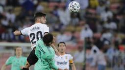 Bek Real Madrid, Varane, berebut bola dengan pemain Valencia, Ferran Torres, pada laga Piala Super Spanyol di Stadion King Abdullah Sport City, Arab Saudi, Rabu (8/1/2020). Real Madrid menang 3-1 atas Valencia. (AP/Amr Nabil)