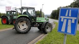 Sebuah traktor milik peternak sapi perah memblokade jalan tol atau jalan bebas hambatan saat melakukan aksi protes di Battice, Belgia, Kamis (30/7/2015). Aksi protes tersebut berkaitan dengan rendahnya harga jual susu. (REUTERS/Francois Lenoir)
