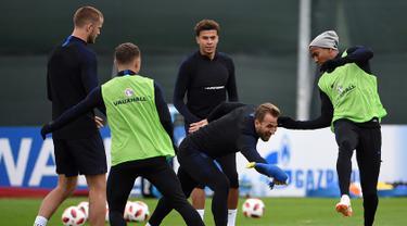 Penyerang Inggris Harry Kane (tengah) memegang mainan ayam di sebelah bek Inggris Ashley Young (kanan) saat mengikuti sesi latihan di Repino (10/7). Inggris akan bertanding melawan Kroasia pada babak semifinal Piala Dunia 2018. (AFP Photo/Ellis)