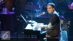 Penyanyi Glenn Fredly memainkan piano saat Konser Tanda Mata Glenn Fredly Untuk Ruth Sahanaya di kawasan Semanggi, Jakarta, Jumat (30/9). Konser ini dipersembahkan untuk 30 tahun Ruth Sahanaya berkarya. (Liputan6.com/Herman Zakharia)