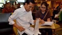 Presiden Jokowi bertanya sambil memeriksa berkas milik masyarakat yang sedang mengurus perizinan, terutama yang terkait penanaman modal asing, Jakarta, Selasa (28/10/14). (Rumgapres/Agus Suparto)