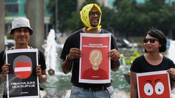 Peserta aksi memegang poster saat aksi peringati hari Hak Asasi Manusia (HAM) 2015 di Bundaran HI, Jakarta, Kamis (10/12/2015). Aksi untuk memperingati Hari HAM Internasional yang jatuh setiap tanggal 10 Desember. (Liputan6.com/Faizal Fanani)