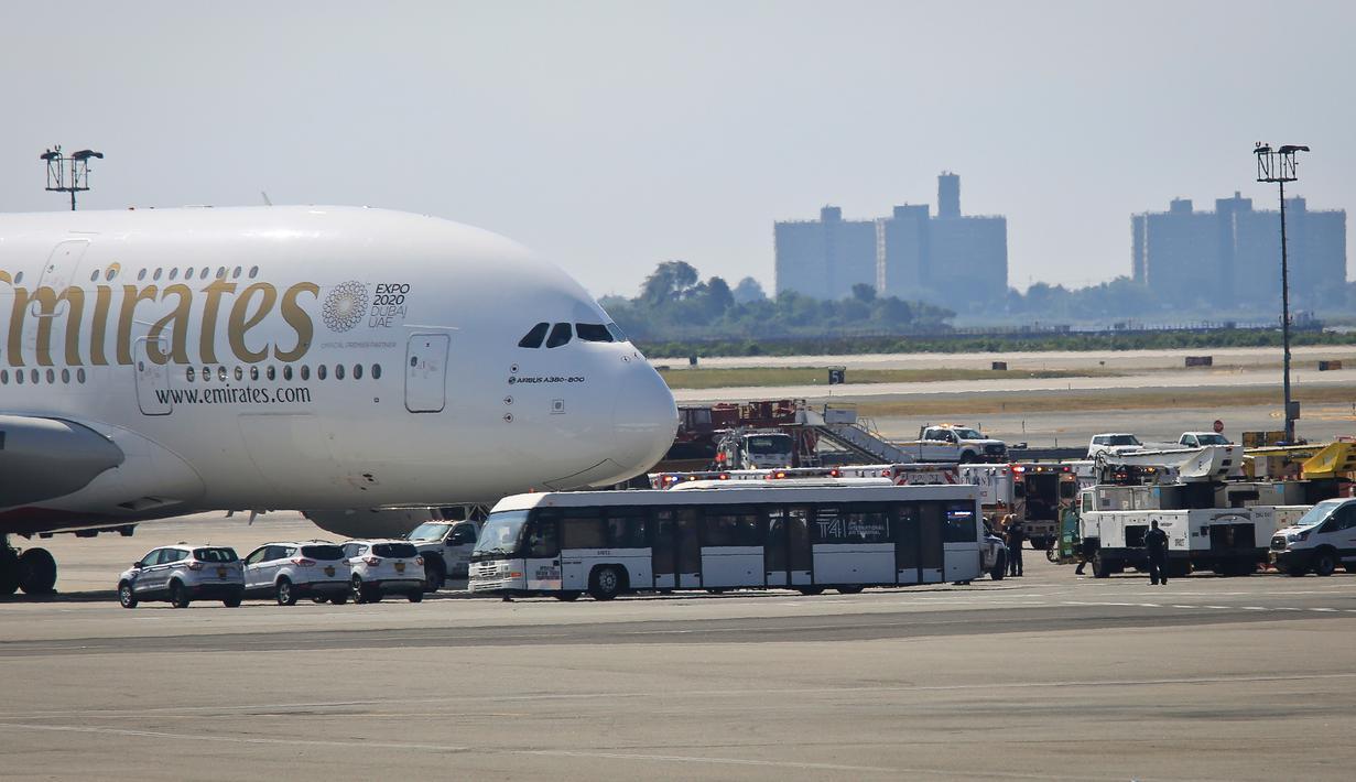 Petugas tanggap darurat berkumpul di luar pesawat setelah penumpang Emirates Airline dilaporkan jatuh sakit di Bandara Kennedy New York, Rabu (5/9). Sekitar 100 dari total 500 penumpang pesawat dari Dubai itu mengeluh sakit dan demam. (AP/Bebeto Matthews)