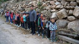 Sejumlah anak berbaris menuju sekolah mereka Desa Atuleer, Tiongkok, Rabu (19/11). Sebelum ada tangga baru, anak-anak harus menempuh perjalanan selama 2 jam menuju ke sekolah yang berada di kaki gunung. (REUTERS)