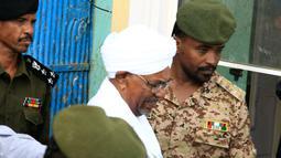 Mantan Presiden Sudan, Omar al-Bashir, dikawal saat keluar dari penjara menuju kantor kejaksaan dalam penyelidikan korupsi di ibu kota Khartoum, Minggu (16/6/2019). Jaksa mengatakan timbunan mata uang asing ditemukan dalam karung gandum di rumah Bashir saat ia dikudeta. (Yasuyoshi CHIBA/AFP)