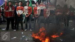 Aksi teaterikal di depan Gedung DPR, Senayan, Jakarta, Rabu (28/10/2015). Dalam aksinya para mahasiswa membakar ban. (Liputan6.com/Johan Tallo)
