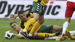 Pemain Polandia, Arkadiusz Milik (kiri) jatuh saat berebut bola dengan pemain Lituania, Modestas Vorobiovas pada laga uji coba di Stadion Narodowy, Warsaw, Polandia, (12/6/2018). Polandia menang 4-0. (AP/Czarek Sokolowski)