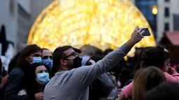 Orang-orang berpose di sebuah pasar Natal di pusat kota Beirut, Lebanon, pada 13 Desember 2020. Baru-baru ini, berbagai dekorasi Natal telah dipasang di pusat kota Beirut menyambut liburan Natal dan Tahun Baru mendatang meski sedang dilanda pandemi COVID-19 dan krisis ekonomi. (Xinhua/Bilal Jawich)