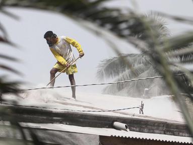 Seorang pria membersihkan atap rumah yang diselimuti abu vulkanik Gunung Sinabung di Karo, Sumatra Utara (20/2). Gunung Sinabung meletus kembali tanggal 19 Februari, yang mengeluarkan asap tebal setinggi sekitar 5.000 meter. (AFP Photo/Kadri Boy Tarigan)