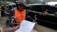 Polisi memeriksa surat tugas pemilik kendaraan bermotor pada Pos Penyekatan Lebaran 2021 di Ciloto, Cianjur, Jawa Barat (9/5/2021). Pos penyekatan ini ditujukan kepada kendaraan para pemudik yang selanjutnya akan memutar balik para pemudik dalam upaya pengendalian COVID-19. (merdeka.com/Arie Basuki)