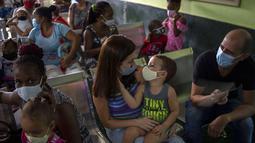 Orang tua menunggu bersama anak mereka untuk menerima dosis vaksin COVID-19 Soberana-02 di sebuah klinik di Havana, Kuba, Kamis (17/9/2021). Pemerintah Kuba memulai vaksinasi Covid-19 bagi anak-anak berusia 2 tahun dengan vaksin buatan dalam negeri. (AP Photo/Ramon Espinosa)