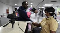 Anggota staf Layanan Kesehatan Port berdiri di sebelah pemindai termal saat penumpang tiba di Bandara Internasional Murtala Mohammed di Lagos, Nigeria, pada 27 Januari 2019. (AFP)