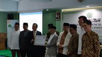 (Memegang plakat) Kepala TETO John Chen dan Ketua MUI KH Ma'ruf Amin, dalam penyerahan simbolis bantuan kemanusiaan dari Taiwan untuk korban gempa-tsunami di Sulawesi Tengah (9/10). MUI bertindak sebagai penyalur bantuan. (Rizki Akbar Hasan/Liputan6.com)