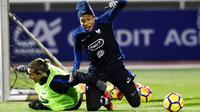 Striker Prancis, Kylian Mbappe dan Antoine Griezmann, terjatuh saat mengikuti sesi latihan jelang laga persahabatan di Paris, Selasa (7/11/2017). Prancis akan berhadapan dengan Jerman dan Wales. (AFP/Franck Fife)