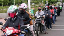 Antrean pengendara motor saat uji emisi gratis di Jakarta Barat, Rabu (13/1/2021). Dinas Lingkungan Hidup DKI Jakarta mengumumkan kendaraan yang tidak mengikuti uji emisi atau tidak lulus uji emisi gas buang akan dikenakan disinsentif tarif parkir yang tinggi dan tilang. (Liputan6.com/Angga Yuniar)