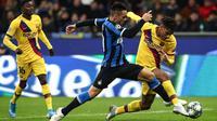 Striker Inter Milan, Lautaro Martinez, berebut bola dengan bek Barcelona, Jean-Clair Todibo, pada laga Liga Champions di Stadion San Siro, Milan, Selasa (10/12). Inter kalah 1-2 dari Barcelona. (AFP/Isabella Bonotto)