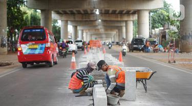 Pekerja menyelesaikan pembuatan separator atau pembatas jalan di Jalan Margasatwa, Andara, Jakarta Selatan, Kamis (21/11/2019). Separator itu dibuat guna memisahkan dua lajur sehingga meminimalisasi tingkat kecelakaan. (Liputan6.com/Immanuel Antonius)