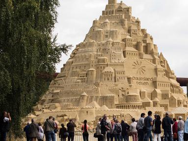 Seniman saat menyelesaikan istana pasir di Landschaftspark di Duisburg, Jerman , (1/9). Seniman dari Duisburg burusaha meraih Guinness Book of World Records dengan membuat istana pasir tertinggi yang pernah ada. (Marcel Kusch / dpa via AP)