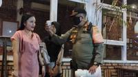 Seorang pengunjung kafe di Kota Palembang, mendapat sanksi menyanyikan lagu nasional, setelah kedapatan tim Satpol-PP Sumsel tidak membawa masker (Liputan6.com / Nefri Inge)