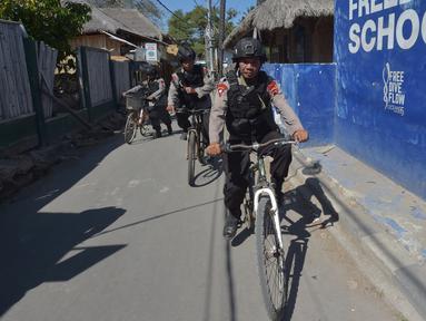 Polisi bersepeda berpatroli di kawasan wisata Pulau Gili Air, Lombok, Nusa Tenggara Barat (NTB), Sabtu (11/8). Patroli dilakukan setelah gempa 7 skala Richter melanda Lombok pada 5 Agustus lalu. (Adek BERRY/AFP)