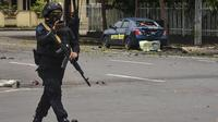Polisi memeriksa lokasi di dekat sebuah gereja setelah ledakan di Makassarr (28/3/2021).   Polisi menduga ledakan terjadi akibat bom bunuh diri. (AFP/Indra Abriyanto)