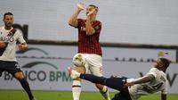 Striker AC Milan, Zlatan Ibrahimovic, dihadang oleh pemain Bologna, Stefano Denswil, pada laga Serie A di Stadion San Siro, Sabtu (18/7/2020). AC Milan menang dengan 5-1 atas Bologna. (AP/Luca Bruno)