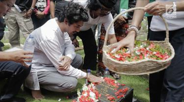 Aktor Reza Rahadian menaburkan bunga di makam Benyamin Sueb di Karet Bivak, Jakarta, Jumat (26/1). Ziarah tersebut ditemani anak ketiga almarhum, H. Beni dan para fans, Benyamin Sueb Fans Club. (Liputan6.com/Faizal Fanani)