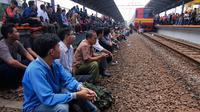 Sejumlah calon penumpang kereta menduduki rel untuk menutup jalur kereta api di stasiun Bekasi, Jawa Barat. (ANTARA FOTO/Hafidz Mubarak)