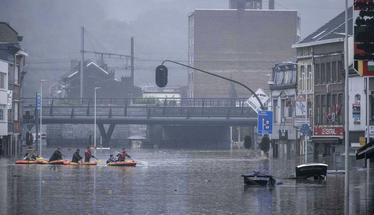 Warga menggunakan rakit karet di tengah banjir setelah Sungai Meuse jebol saat banjir besar di Liege, Belgia, Kamis (15/7/2021). Curah hujan yang tinggi menyebabkan banjir di beberapa provinsi di Belgia dengan hujan diperkirakan berlangsung hingga Jumat. (AP Photo/Valentin Bianchi)