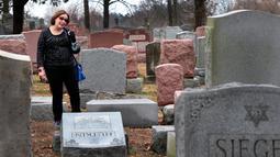 Sally Amon, melihat batu nisan neneknya yang dirusak di Chesed Shel Emeth Cemetery di University City, St Louis, Missouri, (21/2). Setidaknya lebih dari 100 batu nisan rusak di pekuburan itu. (Robert Cohen /St. Louis Post-Dispatch via AP)