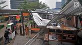 Pedagang mengevakuasi barang-barang kios Rasuna Garden Food Street usai roboh akibat angin kencang, Kuningan, Jakarta, Senin (10/12). Hujan disertai angin kencang menerbangkan sekaligus merobohkan atap dan sebagian bangunan. (Merdeka.com/Iqbal Nugroho)