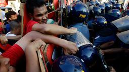 Demonstran berhadapan dengan polisi anti huru-hara ketika aksi protes pada May Day 2016 atau Hari Buruh Sedunia di depan Kedutaan Besar AS di Manila, Filipina, Minggu (1/5). (REUTERS/Czar Dancel)