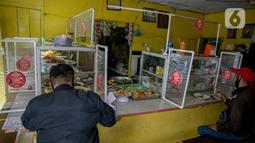 Warga menyantap makanan di warteg kawasan Jakarta, Rabu (27/1/2021). Komunitas Warteg Nusantara (Kowantara) menyatakan, sekitar 50 persen atau 20.000 unit warteg di Jabodetabek akan gulung tikar tahun ini disebabkan tidak mampu membayar atau memperpanjang sewa tempat. (Liputan6.com/Faizal Fanani)