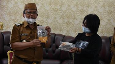 Bupati Gorontalo Utara, Indra Yasin bersama Arkeolog asal Sulawesi Utara menunjukan koin Emas yang ditemukan di Benteng Mass (Arfandi Ibrahim/Liputan6.com)