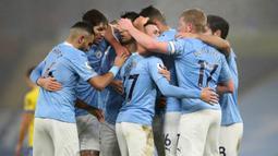 Para pemain Manchester City merayakan gol yang dibuat gelandang Phil Foden (tengah) ke gawang Brighton and Hove Albion dalam laga lanjutan Liga Inggris 2020/21 di Etihad Stadium, Rabu (13/1/2021). Manchester City menang 1-0 atas Brighton. (AFP/Clive Brunskill/Pool)
