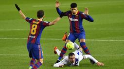 Striker Eibar, Kike Garcia (bawah) terjatuh usai perebutan bola dengan bek Barcelona, Ronald Araujo (kanan) dalam laga lanjutan Liga Spanyol 2020/21 pekan ke-16 di Camp Nou, Selasa (29/12/2020). Eibar bermain imbang 1-1 dengan Barcelona. (AFP/Pau Barrena)