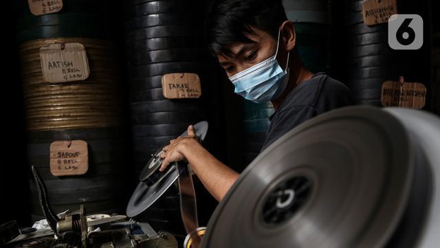 Adul (29) menyiapkan film seluloid 35mm untuk pertunjukan layar tancap di gudang rumahnya di Jakarta, Rabu (28/4/2021). Biasanya Adul dan ayahnya menyewakan peralatan dan film seluloid 35mm untuk layar tancap dengan harga Rp50 ribu sampai Rp200 ribu saja. (Liputan6.com/Johan Tallo)