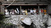 Deretan boneka kayu yang dikenal sebagai Tau Tau didandani dengan pakaian adat Toraja dan dipajang untuk mewakili bangsawan yang telah meninggal di Londa, Kabupaten Tana Toraja (11/09/2018) (AFP/Goh Chai Hin)