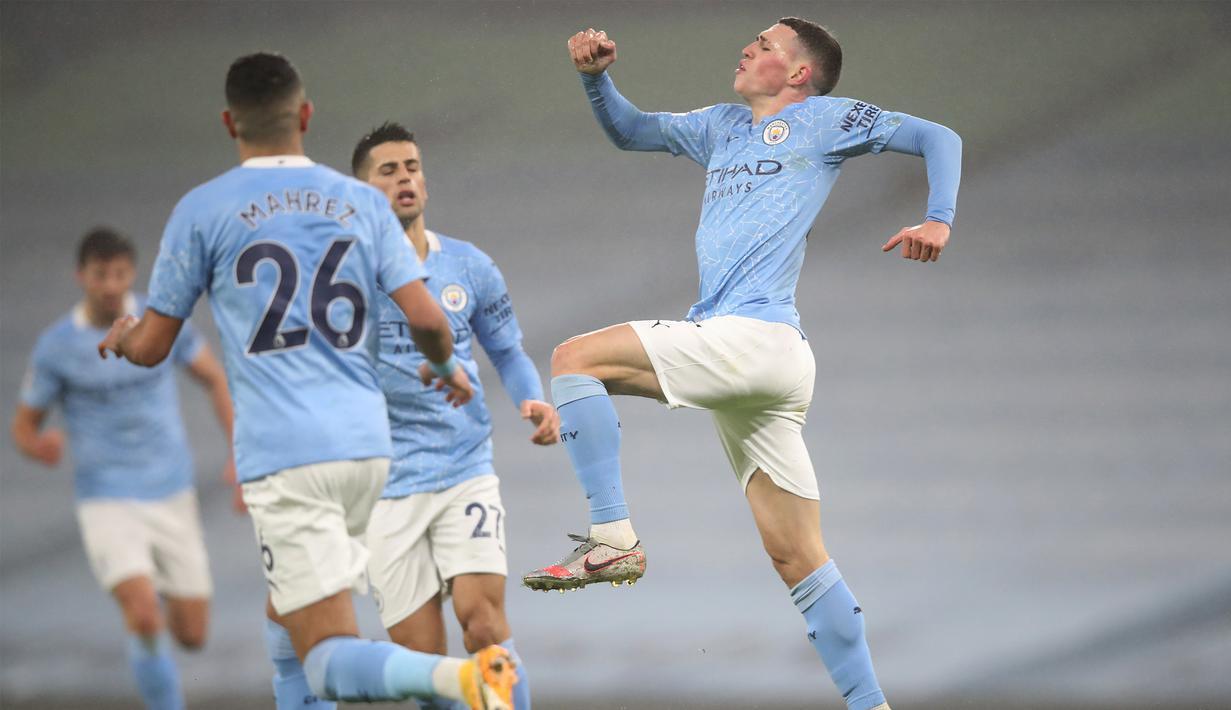 Gelandang Manchester City, Phil Foden (kanan) melakukan selebrasi usai mencetak gol ke gawang Brighton and Hove Albion dalam laga lanjutan Liga Inggris 2020/21 di Etihad Stadium, Rabu (13/1/2021). Manchester City menang 1-0 atas Brighton. (AFP/Clive Brunskill/Pool)