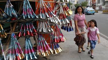 Seorang anak melihat terompet di kawasan Kota Tua, Jakarta. Selasa (27/12). Terompet tersebut dijual dengan harga bervariasi, mulai dari Rp3ribu hingga Rp15ribu, tergantung bentuk dan ukurannya. (Liputan6.com/Immanuel Antonius)