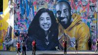 Orang-orang mengabadikan mural Kobe Bryant dan Putrinya Gigi buatan seniman Prancis Mr. Brainwash di Los Angeles (31/1/2020). Bryant memenangkan lima gelar juara NBA dan peraih medali emas Olimpiade dua kali. (AFP/Chris Delmas)