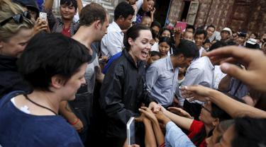 Utusan khusus UNHCR, Angelina Jolie (tengah) berjabat tangan dengan sejumlah pengungsi etnis Kachin saat melakukan kunjungan ke ibukota Myitkyina, Myanmar, Rabu (30/7/2015). (REUTERS/Soe Zeya Tun)