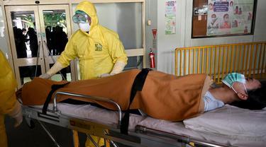 Tim medis mengevakuasi pasien suspect virus corona pada kegiatan simulasi di Rumah Sakit Umum Pusat (RSUP) Sanglah, Denpasar, Rabu (12/2/2020). Simulasi tersebut untuk menunjukkan kesiapan sekaligus menyegarkan kembali pengetahuan SDM dalam menangani virus Corona. (SONNY TUMBELAKA/AFP)