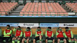 Para pemain Jeonbuk Hyundai Motors di bangku cadangan saat melawan Suwon Samsung Blue Wings pada laga K-League di Stadion Jeonju, Korea Selatan, Jumat (8/5/2020). Kembali bergulir di tengah wabah corona, K-League tanpa penonton. (AFP/Jung Yeon-Je)